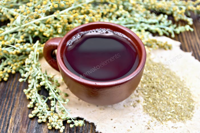 Tea with wormwood in brown cup on dark board