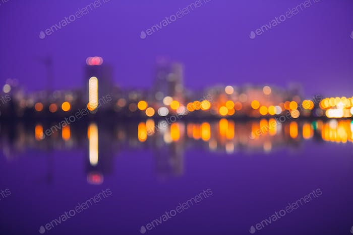 Abstract Blurred Bokeh Urban Backdrop With Reflections In Water.