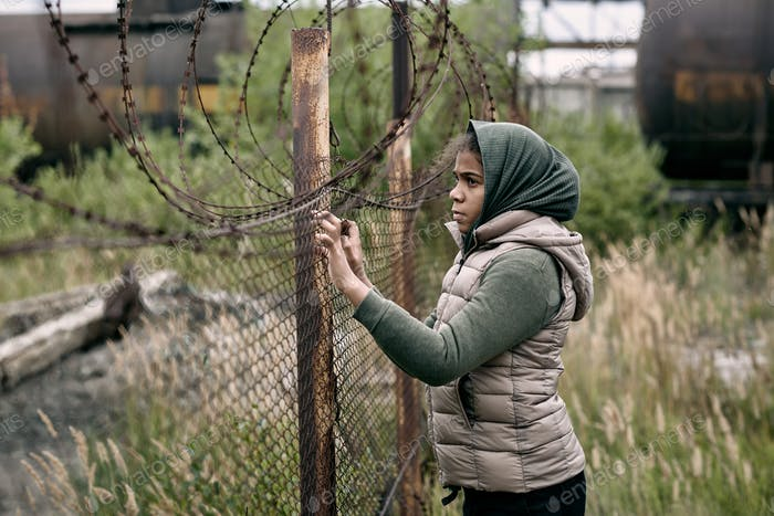 Homeless girl in casualwear standing by barb wire fence