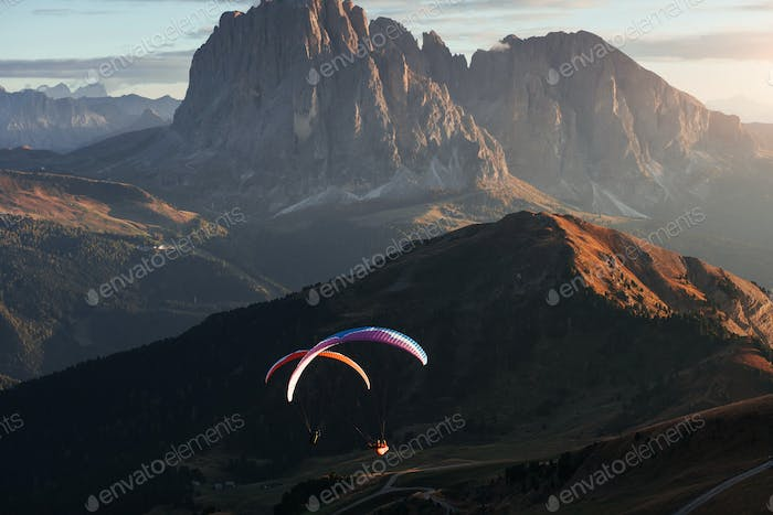 The Seceda dolomites and two paragliders on the sunset lights