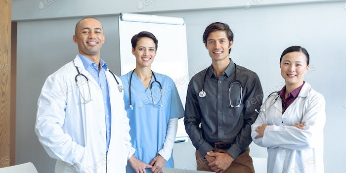 Front view of happy diverse medical team looking at camera in conference room of hospital