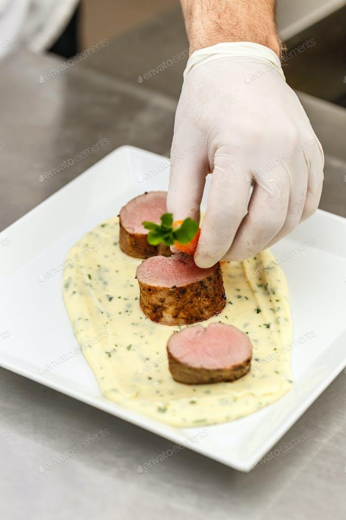 Chef garnishing meat plate