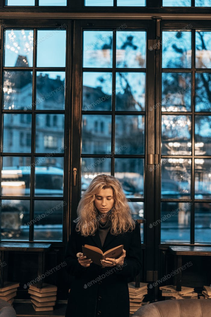 Woman reading a book on the background of window