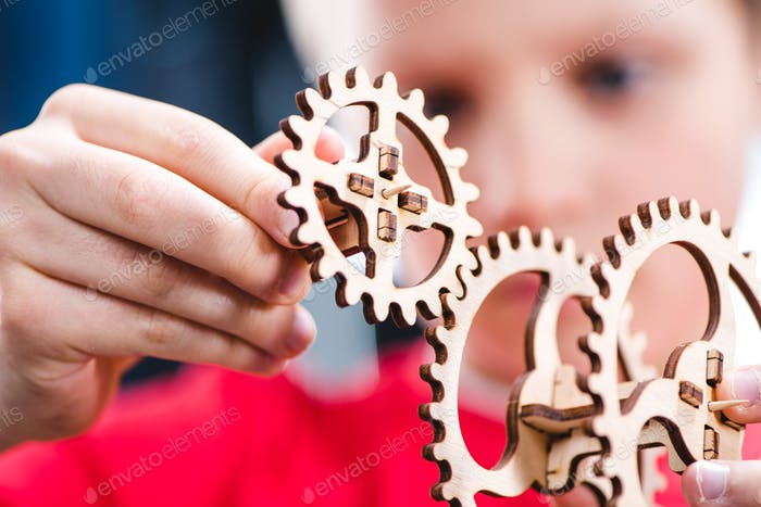 Close-up view of kid holding wooden gear mechanical toy