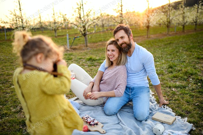 Small girl with camera taking photograph on family picnic outdoors in nature