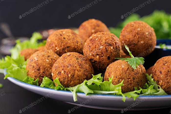 Falafel, hummus and pita. Middle eastern or arabic dishes on a dark background. Halal food.