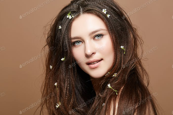 Mädchen mit vielen kleinen Blumen in langen Haaren