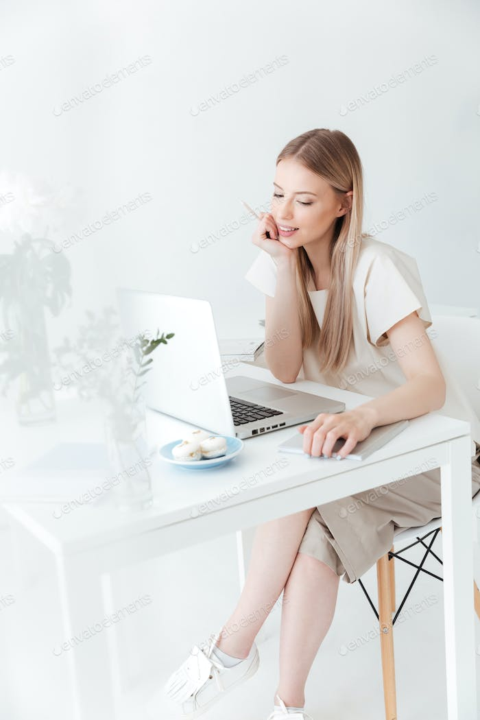 Cheerful woman sitting indoors using laptop