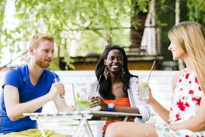Junge und glückliche Freunde sitzen am Tisch