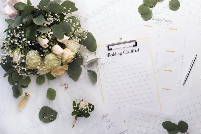 Leere Checkliste mit Planer und Rosenstrauß