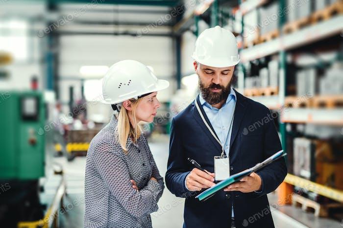 Ein Porträt eines Industriemannes und einer Ingenieurin mit Zwischenablage in einer Fabrik, arbeitet.