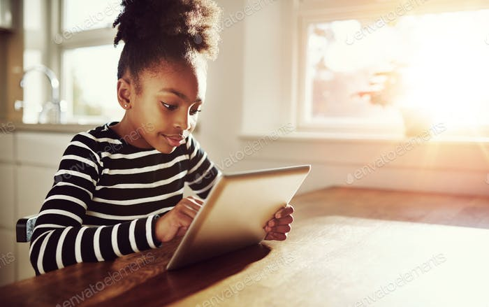 Young black girl browsing on a tablet-pc