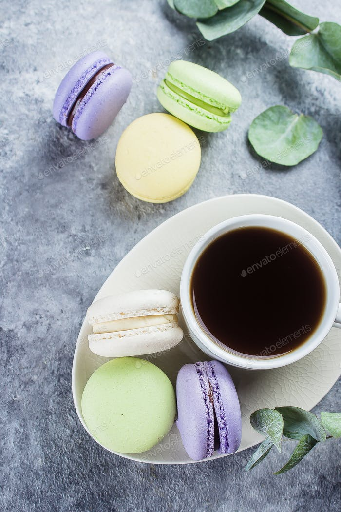 Delicious colorful pastel macarons with cream and coffee cup. Coffee break scene with macaron candy