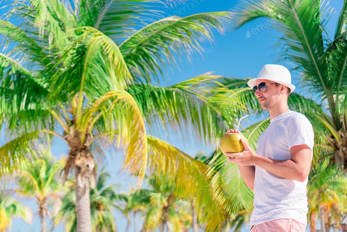 Young man drinking coconut milk during tropical vacation