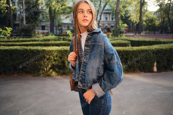 Beautiful stylish casual girl in denim jacket thoughtfully looking away outdoor