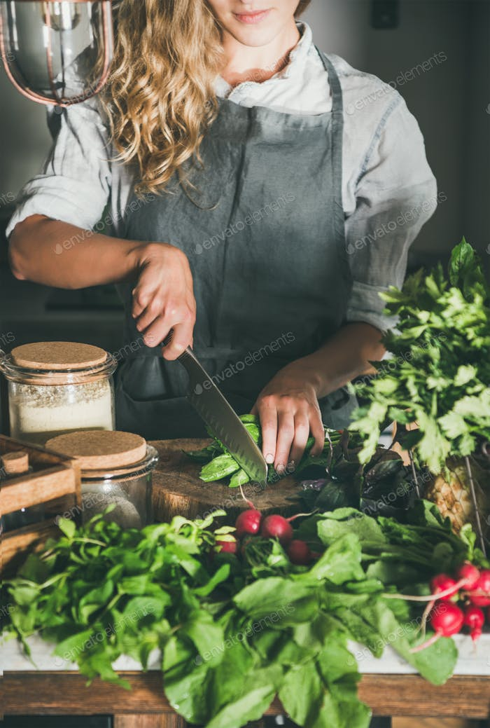Woman cutting green vegetable ingredients on concrete kitchen counter