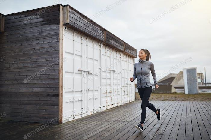 Sportlich junge asiatische Frau läuft im freien an einem bewölkten Tag