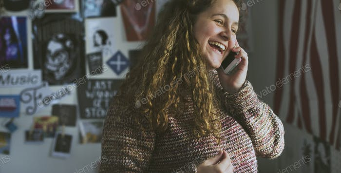 Teenage girl talking on a phone in a bedroom