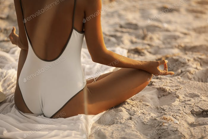 Yoga Meditation Pose with Headphones on the Beach