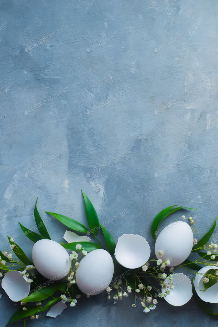 Fresh eggs with green leaves and spring flowers. Floral Easter decoration concept with copy space