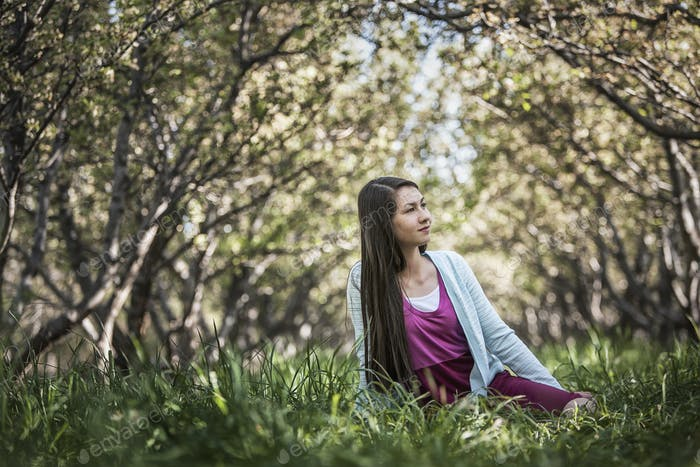 A girl sitting on the grass in a woodland, with trees creating a natural tunnel.