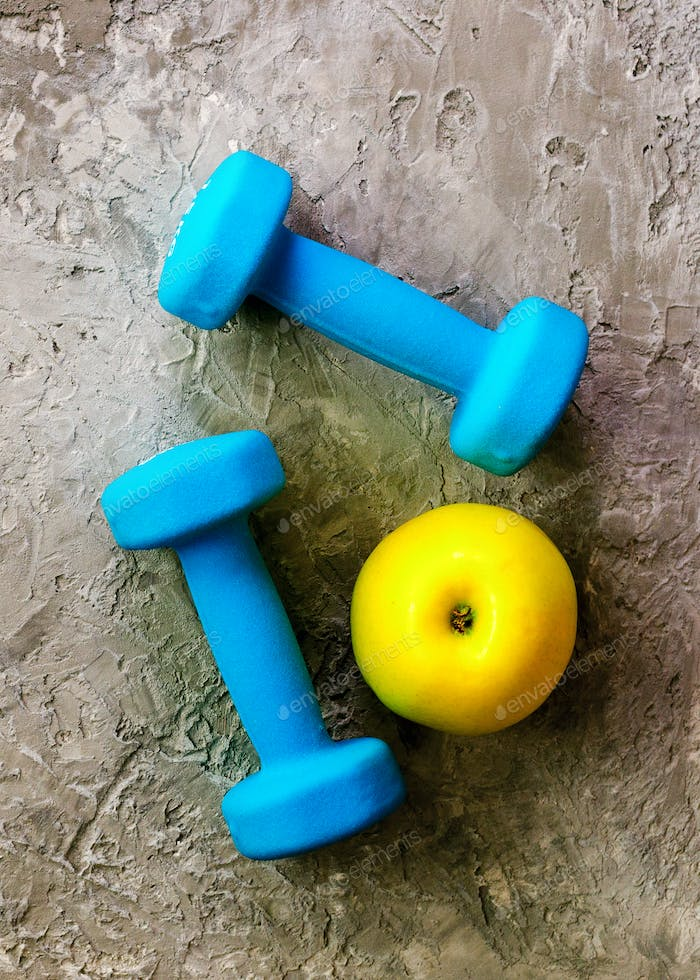 Turquoise dumbbells with measuring tape and yellow apple on concrete background. Free space for your