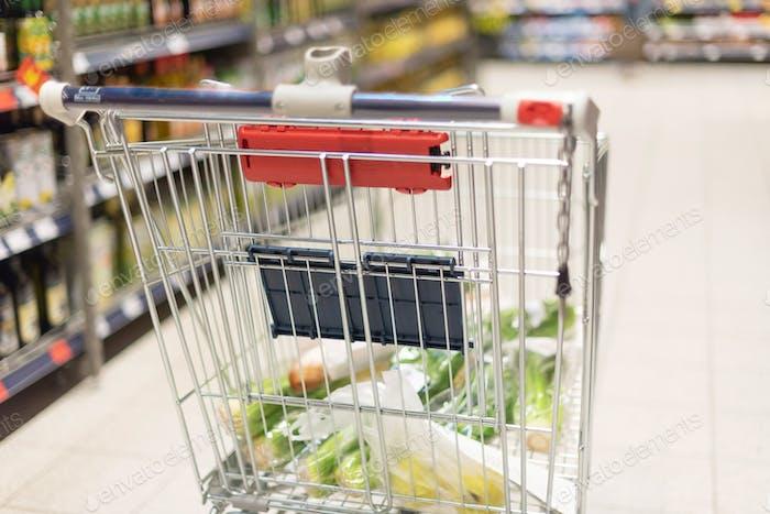 Carrito de la compra lleno de comida en fondo de supermercado borroso. Espacio de copia. Sustentable