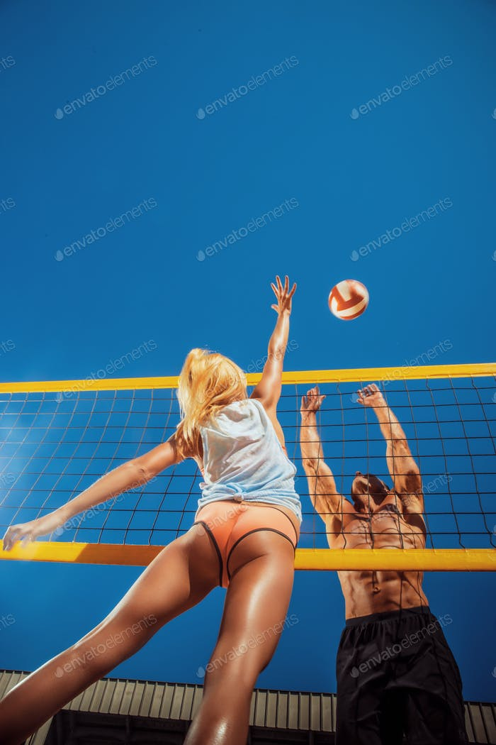 Young people playing volleyball on the beach.
