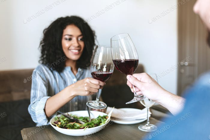 Beautiful African American girl having dinner with friend in restaurant