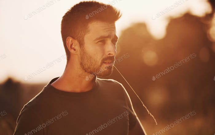 Confident man standing in the field illuminated by sunlight