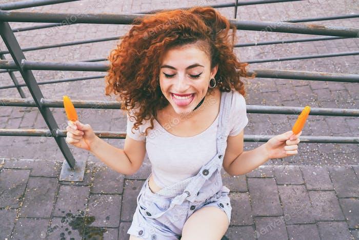 Young redhead woman enjoying ice creams