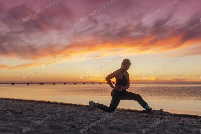 Mujer joven ejercitando en la playa al atardecer