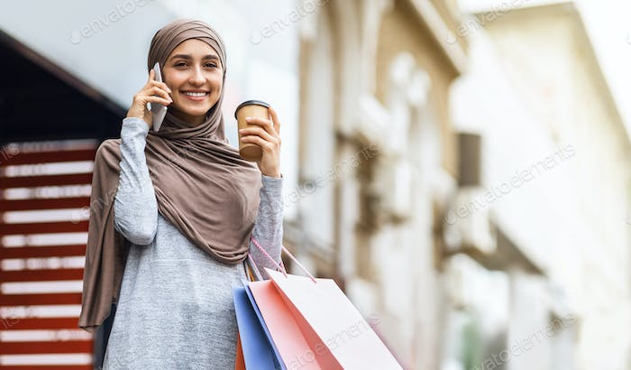 Happy muslim woman with purchases talking on phone