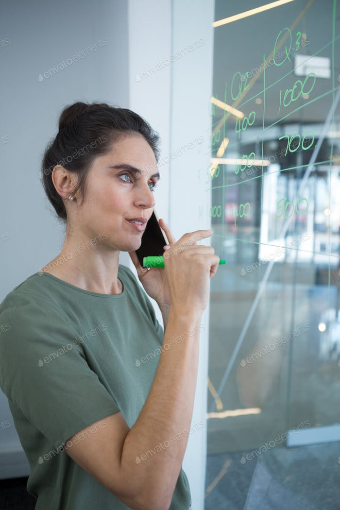 Female executive talking on mobile phone while writing on glass