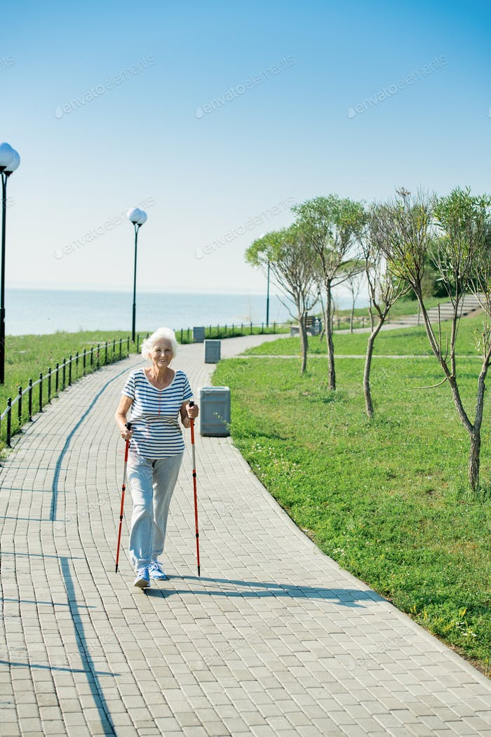 Active Senior Woman Nordic Walking in Park