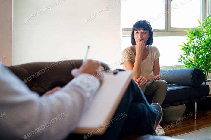 Psychologist taking notes during therapy session.