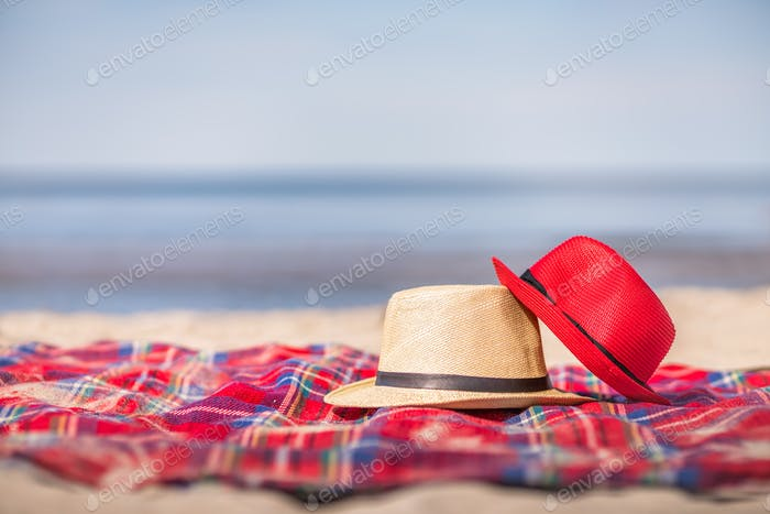 Red and white straw hats on the colorful blanket on the 