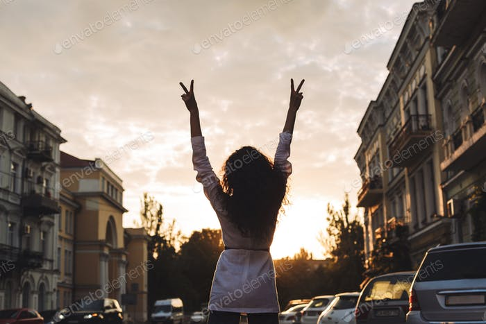 Young woman standing from back on street and holding her hands up while showing peace gesture
