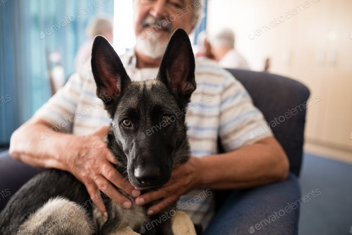 Midsection of senior man holding puppy while sitting on armchair