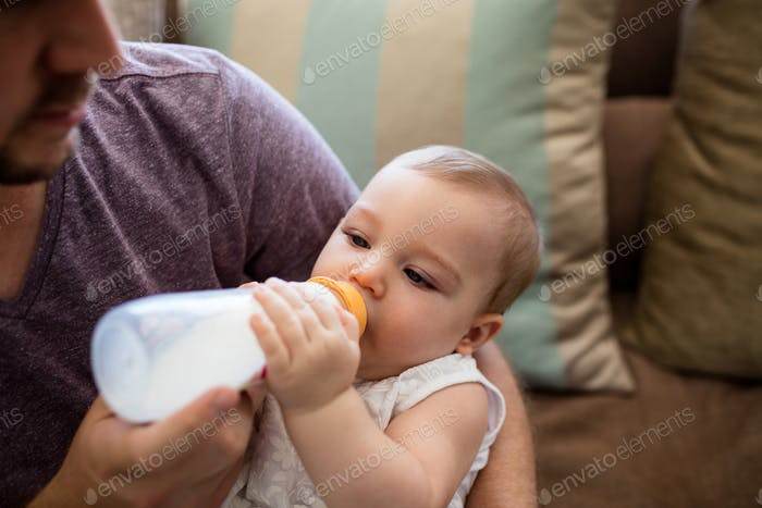 Father feeding milk to baby girl