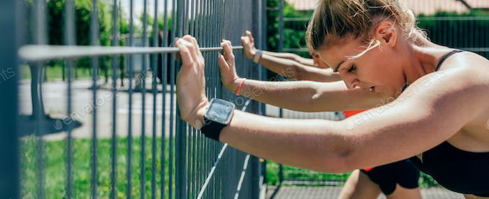 Two sportswomen supported on a fence