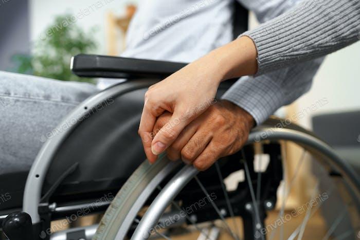 Nahaufnahme einer weiblichen berührenden Hand eines behinderten Mannes im Rollstuhl zur Unterstützung