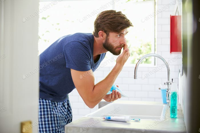 Man In Pajamas Putting On Moisturizer In Bathroom