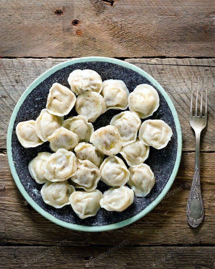 Boiled prepared homemade russian pelmeni, dumplings, ravioli with meat on grey plate with fresh