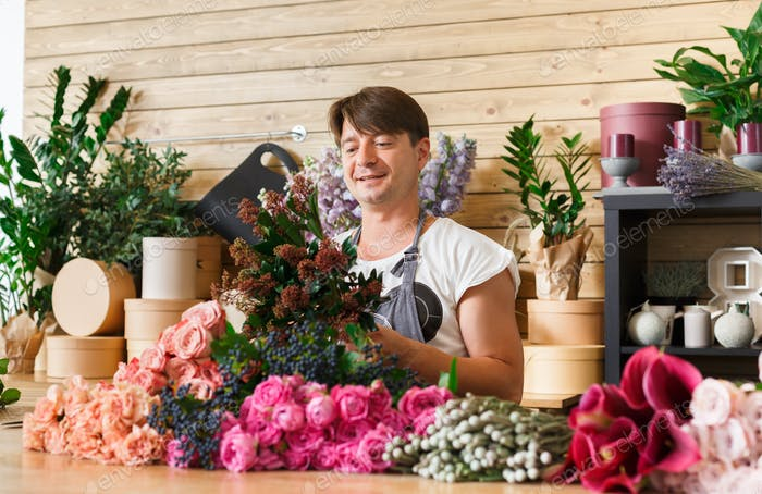 Man florist assistant in flower shop delivery make rose bouquet
