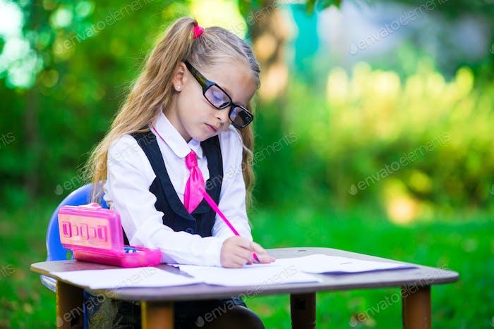 Entzückende kleine Schulmädchen am Schreibtisch mit Notizen und Bleistiften im Freien. Zurück zur Schule