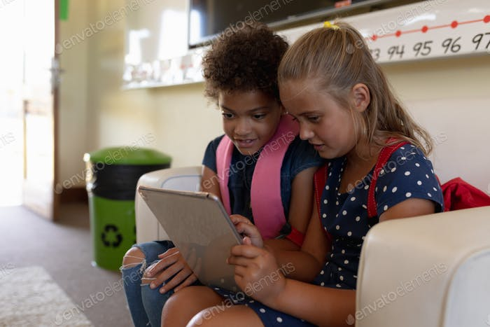 Schoolgirls looking at a tablet computer together in a classroom at elementary school