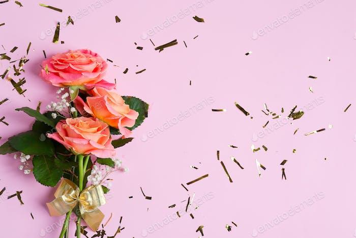 Grußkarte aus natürlichem Blumenstrauß von frisch gepflückten Rosen Blumen auf einem pastellrosa Hintergrund