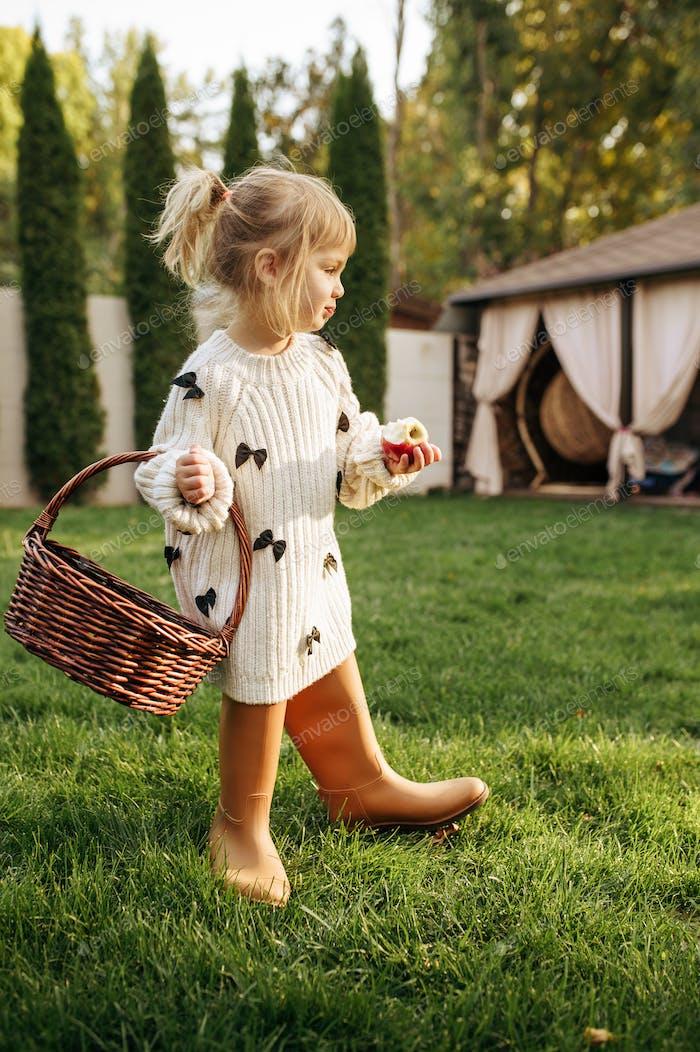 Little girl with basket eats an apple in garden