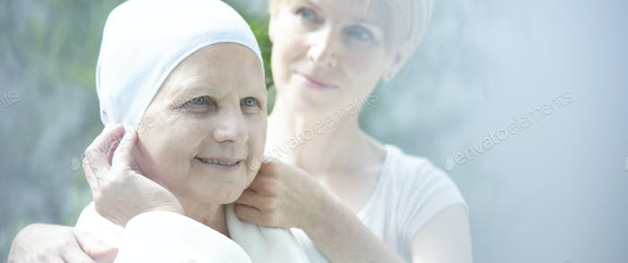 Panorama and flare of smiling sick elderly woman with cancer and